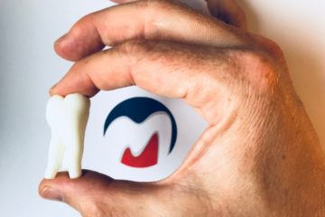 Modell eines Zahnes und Logo der Praxis